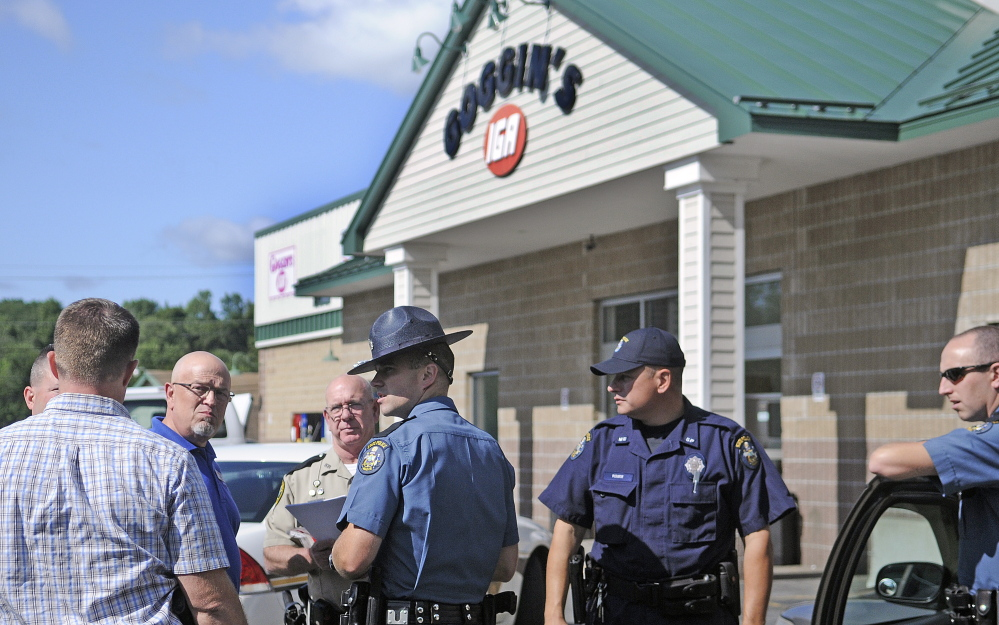 Police interview a witness Monday after Goggin's IGA was robbed in Randolph.