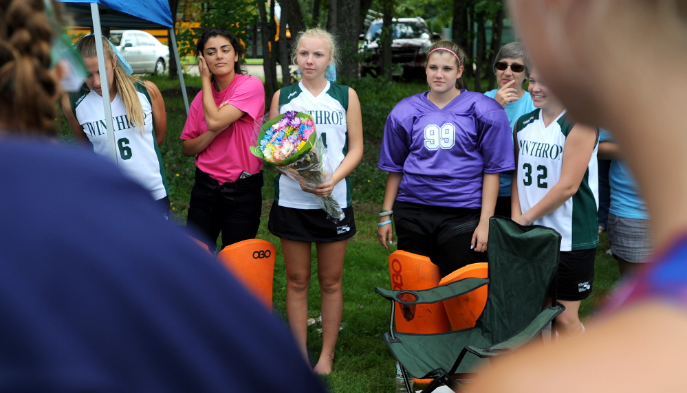 Winthrop High School's Maddie Thomas, center, holds flowers offered by Messalonskee High School in memory of Winthrop's Kelsey Stoneton during Play Day hosted by Winslow High School in Winslow on Saturday.