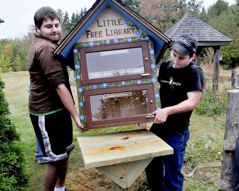 Unity College students and volunteers Thomas Ciarlante, left, and Brett Skelly place a Little Free Library structure on a post at Triplet Park in Unity on Saturday. The work was part of the Unity Barn Raisers' annual Day of Service. Community members worked on the organization's gardens, trails, fall clean-up projects and a pig roast dinner.