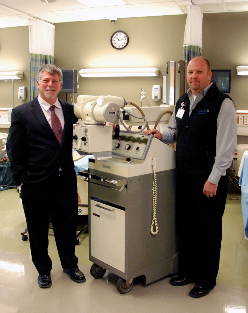 KVCC President Dr. Richard Hopper, left, and MaineGeneral Medical Center Imaging Manager Jeff Trask with the donated X-ray machine in KVCC's TD Simulation Laboratory.