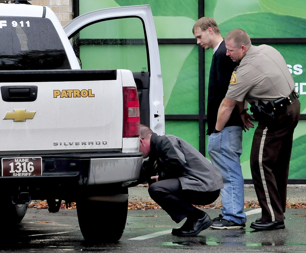 Somerset Deputy Ronnie Blodgett searches a handcuffed man outside the Rite Aid store in Skowhegan following report of a robbery on Wednesday.