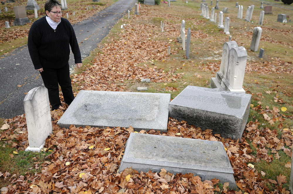Karen Cyr inspects headstones Wednesday that were damaged after an altercation in the Monmouth Ridge Cemetery more than a year ago.