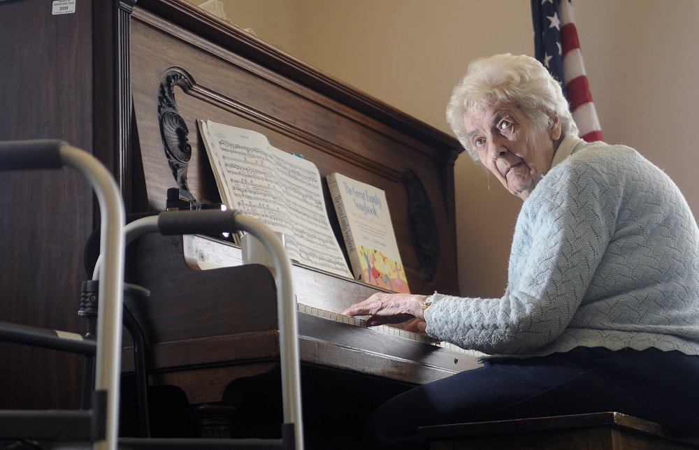 Joyce Fessenden, 83, plays the piano recently during lunch at the William S. Cohen Community Center in Hallowell. Fessenden uses a walker to reach the piano. She has been playing for 70 years to crowds large and small.