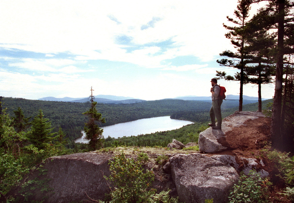 "A Maine forester overlooks Sing Sing Pond along the Turtle Ridge Trail in the Nahmakanta Lake region between Moosehead Lake and Baxter State Park. Under Gov. Paul LePage's proposed timber-harvesting changes for state-owned forestlands, such as the 44,000 acres that make up Nahmakanta Public Reserved Lands, critics fear a dramatic shift in the multiple-use philosophy that has guided management for decades. LePage officials insist the ""underlying, guiding"" principles regarding harvesting on public land won't change."