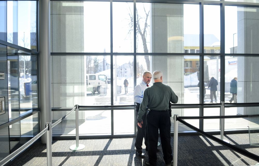 Michael A. Coty, director of judicial marshals, left, speaks with court officer Robert Annese in February while setting up security for the Capital Judicial Center in Augusta.