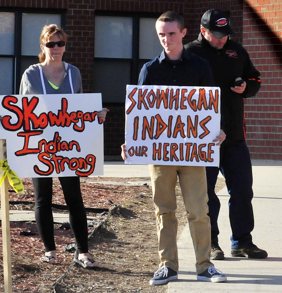 Zach Queenan, holding a sign at right, during a rally in April. Queenan has now changed his mind and is supporting the effort to stop using Indians as a mascot.
