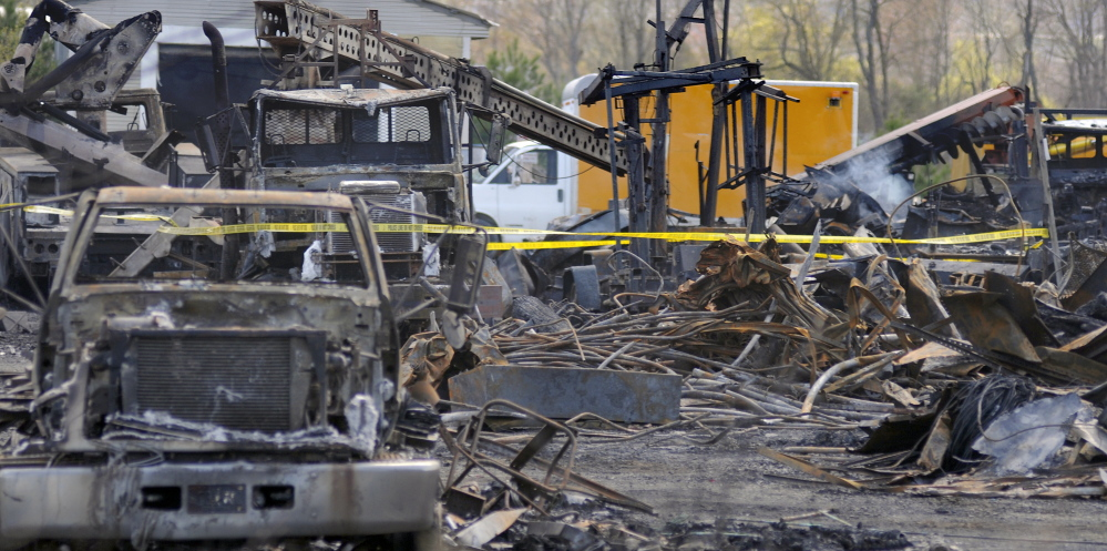 The AD Electric site in Monmouth on Wednesday consisted of charred vehicles and a burned building. The Office of the State Fire Marshal and the Maine Department of Environmental Protection are investigating Tuesday's fire.