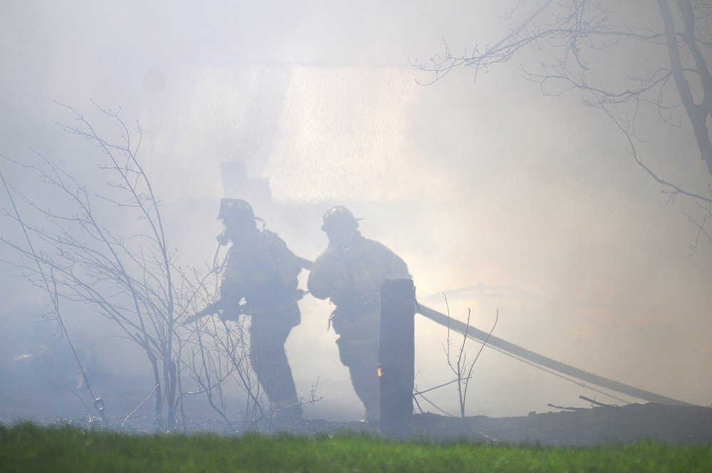Firefighters on Tuesday try to approach the blaze that destroyed AD Electric on South Monmouth Road in Monmouth. The Office of the State Fire Marshal and the Maine Department of Environmental Protection are investigating the fire.