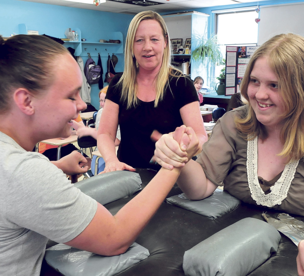 Athens Community School teacher Tammy Moulton watches as eighth-graders Mia Braley, left, and Sylvia Andersen arm wrestle during a community volunteer visit by wrestling instructor Cory Bussell on Thursday.