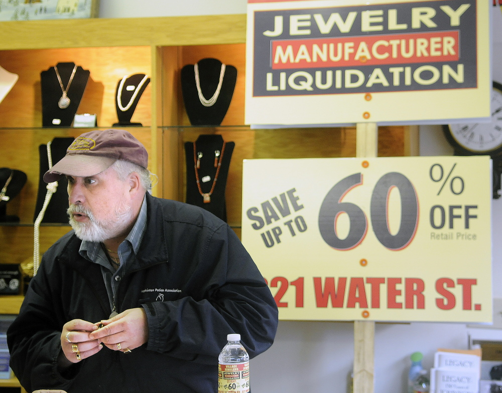 Daniel Lane appraises a ring last week at his Gardiner business, The Village Jeweler, in front of a sign that state officials told him to stop using to advertise a liquidation sale off-premises.