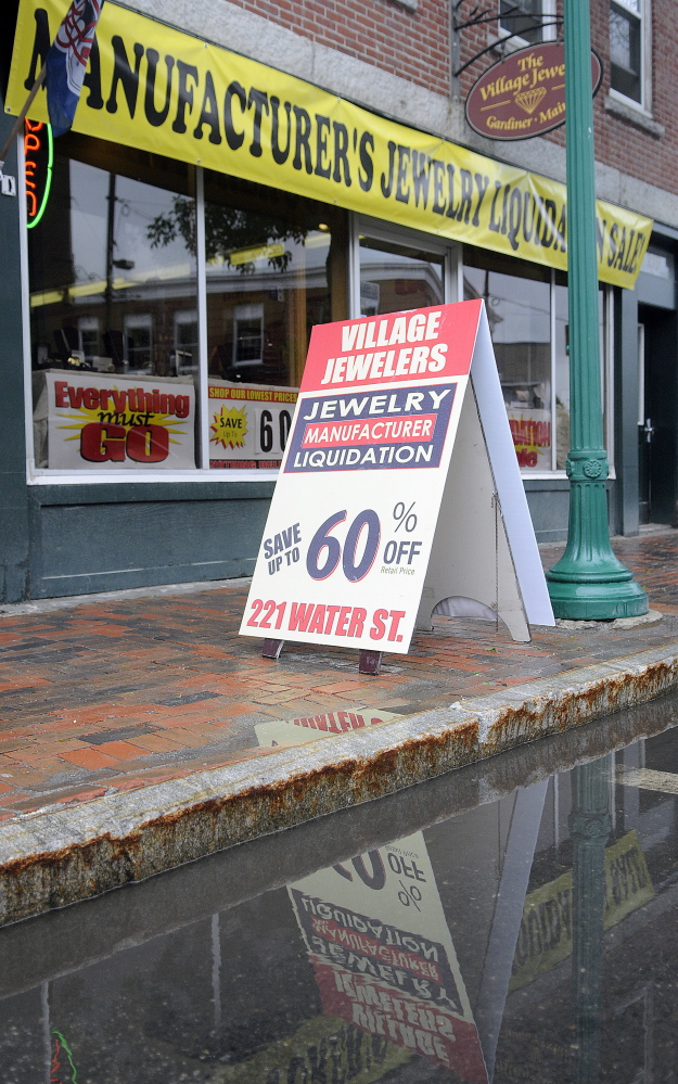 Daniel Lane displays a sign for a discount sale at The Village Jeweler store on the street in front of his business in Gardiner. State officials have told him to stop using sign walkers to advertise a liquidation sale.
