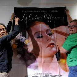 Nancy Bixler, left, and Serena Sanborn hang a movie poster Wednesday on a wall of the Railroad Square Cinema lobby for the Maine International Film Festival in Waterville.