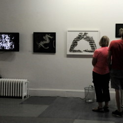 People look at pieces of work that are part of the MIFFONEDGE exhibit at Common Street Arts in Waterville on Sunday.