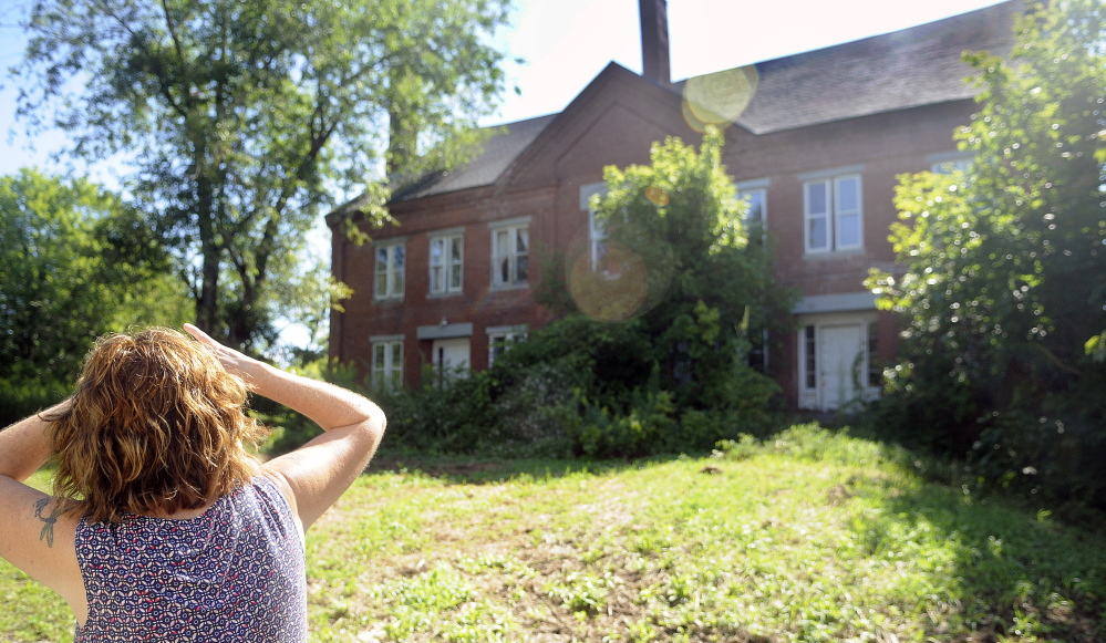 Barbara Bowley inspects the Hathorn Block in Richmond on Thursday. Bowley owns Annabella's Bakery & Cafe with her daughter, Stacy LaBombard, which is across the street from the neglected structure.