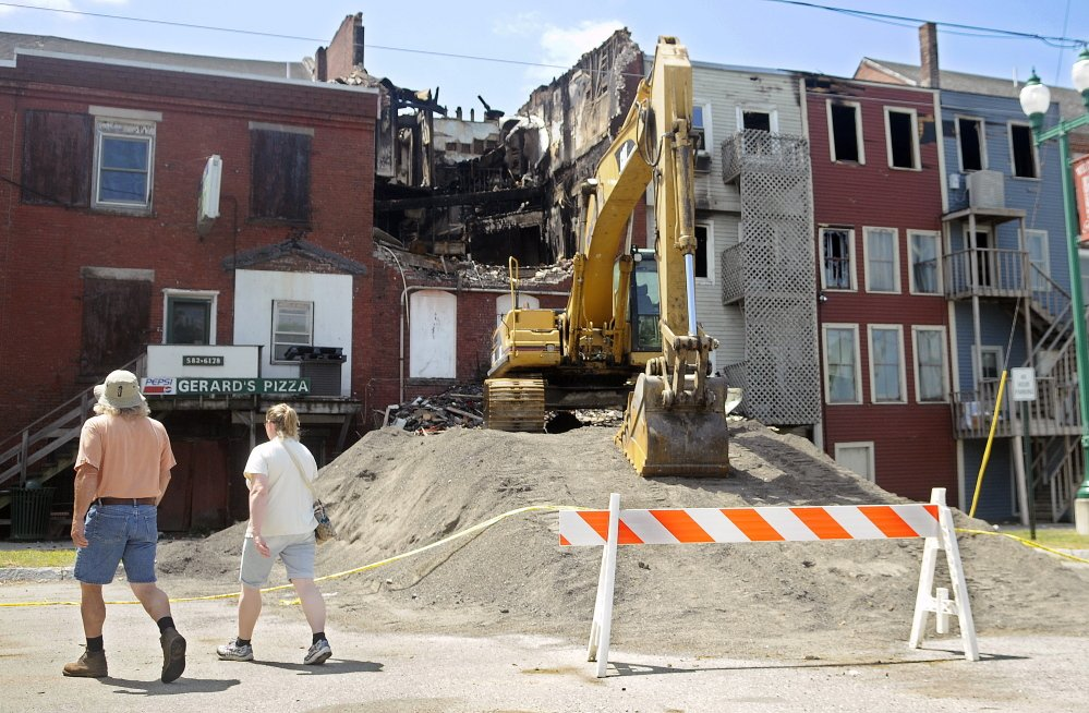 Four days after the July 16 fire, people view the damage from the back side of Water Street buildings in Gardiner.