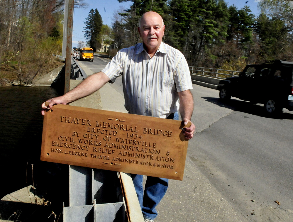 Waterville Public Works Director Mark Turner holds a bronze plaque in May at the Gilman Street bridge. The plaque was recently found and the bridge will be rededicated Thayer Memorial Bridge Saturday.