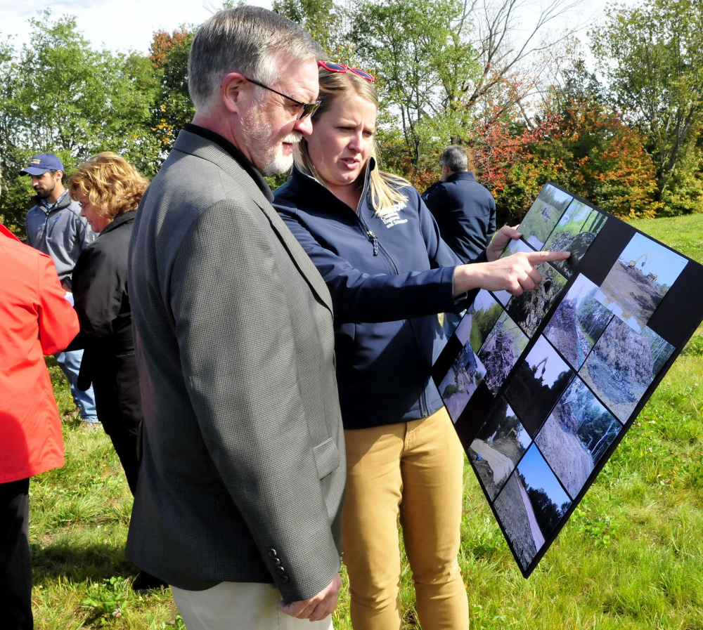 Jamie Madore of Ransom Consultants shows photos of the former Wilton Tannery waste site that is now contained at the site in Wilton on Thursday. Looking on is Dave Mitchell.