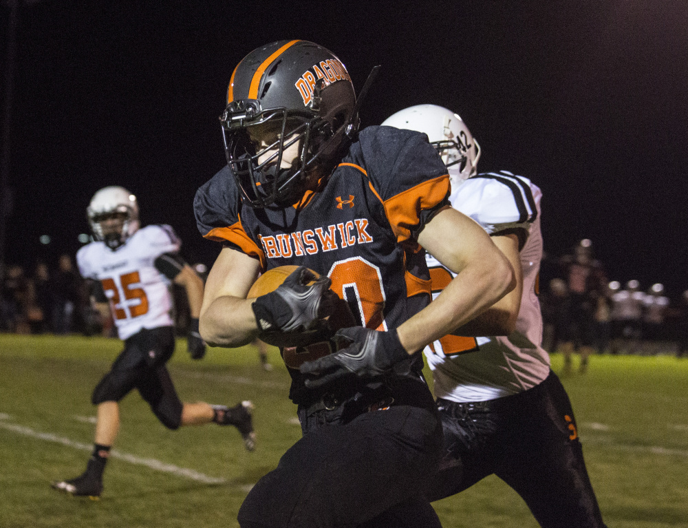 Portland Press Herald photo by Whitney Hayward   Brunswick running back Hunter Garrett runs past Skowhegan defensive lineman Spencer Salley, left, and Jordan Meader during a Pine Tree Conference Class B game Friday night in Brunswick.