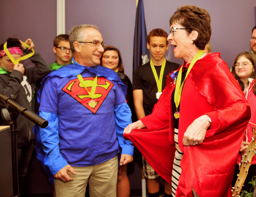 Staff photo by Joe Phelan Boys and Girls Club of Greater Augusta board member Dr. Roy Miller, left, watches as U.S. Sen. Susan Collins models the cape with a lightning bolt and letter C that he presented her Saturday during an awards ceremony at Kaplan University in Augusta. The capes were part of superhero-themed fundraising running events that the club held in the morning.
