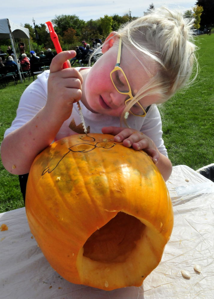 Payten Frederick uses a safety knife to carve a pumpkin Sunday during the Harvest Fest and Festival of the Falls event in Waterville.