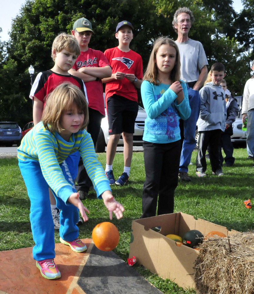Abigail Taylor bowls a pumpkin Sunday during an event of the Harvest Fest and Festival of the Falls in Waterville.