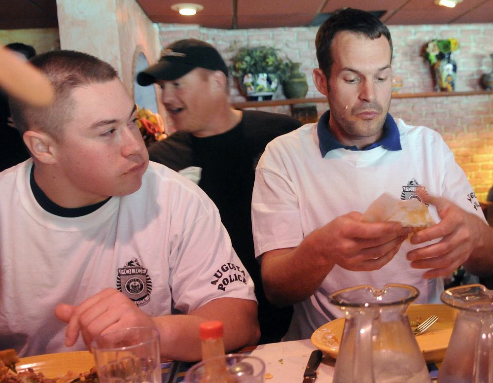 The Augusta Police Department's animal control officer, Francois Roodman, right, wipes his hands Sunday after winning a taco eating contest between the Waterville and Augusta police.
