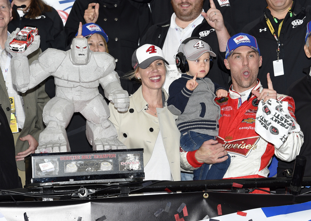 Kevin Harvick, right, celebrates and poses with the trophy in Victory Lane with his son Keelan, second from right, and wife DeLana, left, after he won the NASCAR Sprint Cup race Sundayat Dover International Speedway in Dover, Del.