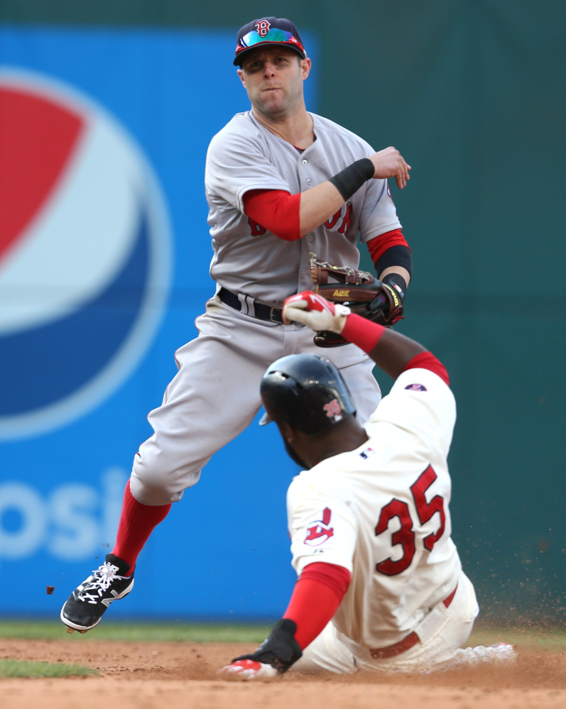 Boston's Dustin Pedroia, top, turns a double play over Cleveland's Abraham Almonte, bottom, by throwing out Roberto Perez at first base during the sixth inning Sunday in Cleveland.