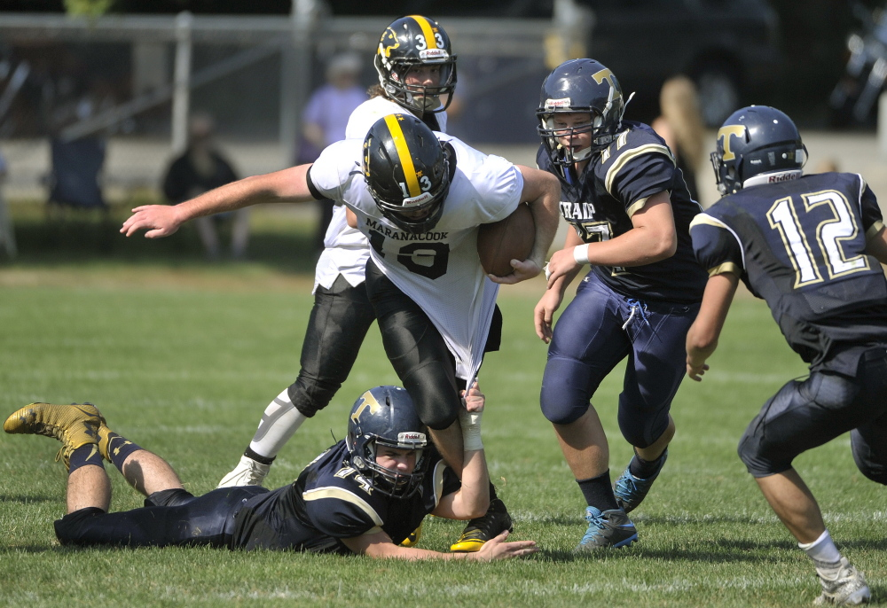 Portand Press Herald photo by John Ewing   Maranacook quarterback Kyle Morand tries to break free from a host of Traip defenders, inlcuding Justin Barnaby (74), Shelton Thomas (57) during a game last month in Kittery.