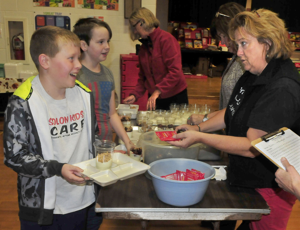 "Solon Elementary School student Hunter Sousa accepts a snack from teacher Michelle Stevens after students took part in the Walking School Bus Tuesday. Asked what he thought of the walk Sousa said, ""It's fun and I like hanging out with my friends."""
