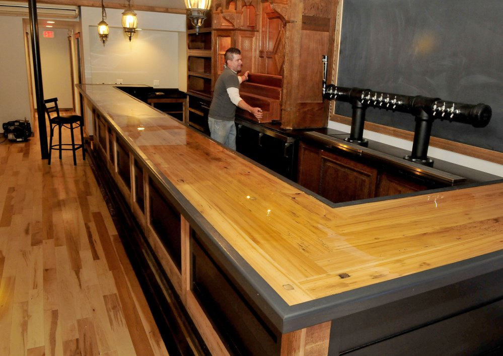 Woodworker Dustin Burphy centers a piece of antique wood cabinetry into the shelves behind the bar at the new Tucks Ale House in Farmington on Monday. Much of the interior is from reclaimed materials.