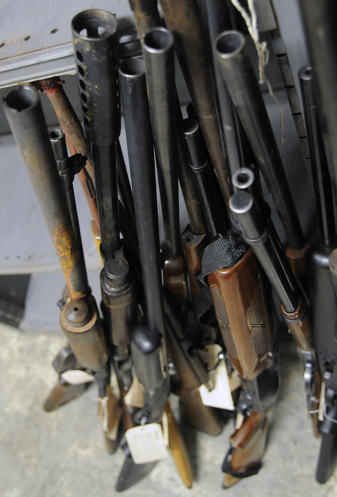 Rifles and shotguns are seen in storage Wednesday at Augusta police headquarters.