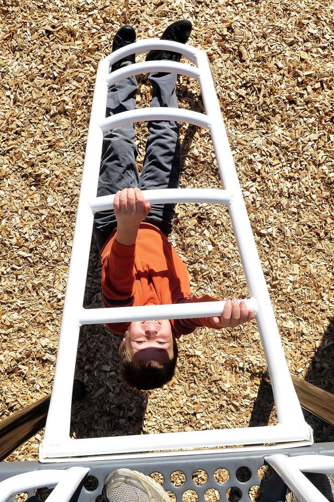 As seen from the top of new playground equipment, Canaan Elementary School student Joshua Rairdon makes his way up underneath a ladder on Thursday.