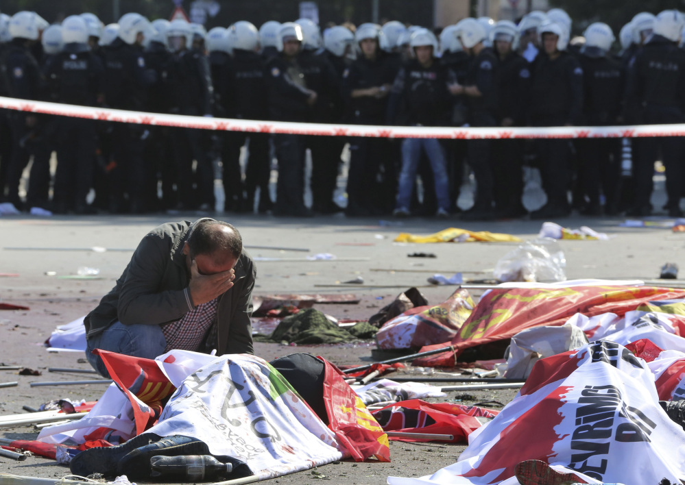 A man cries over the body of a victim, at the site of an explosion in Ankara, Turkey, Saturday.
