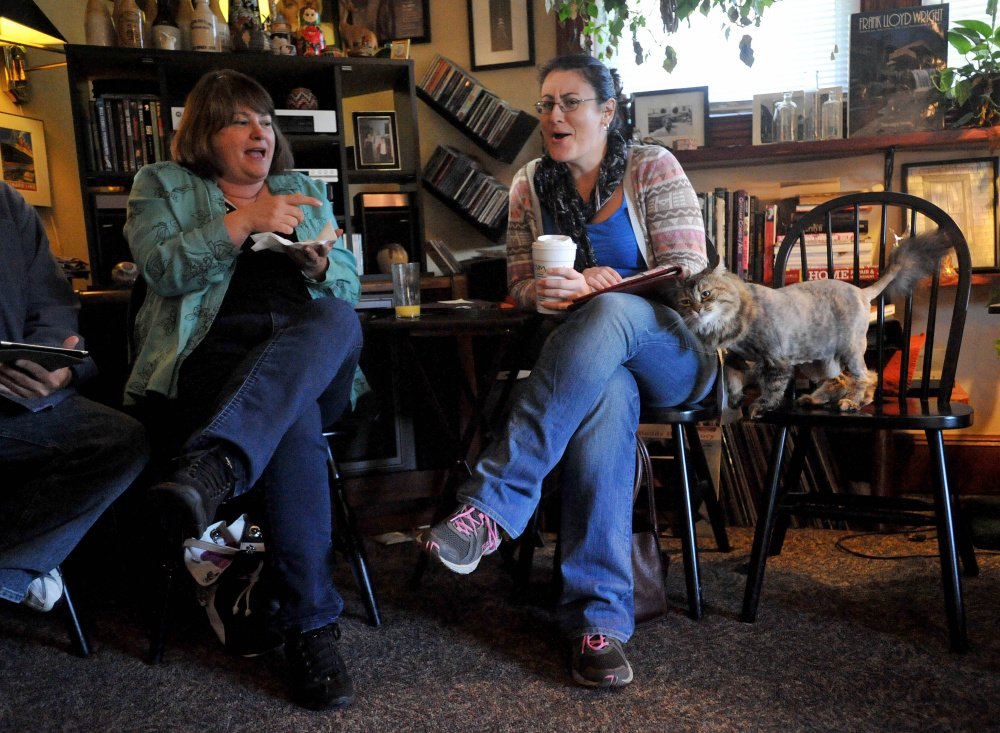 May, a Maine coon cat, cuddles up with Anna Holderman on Saturday during a South End Neighborhood Association meeting at the home of Chris Moody on Summer Street in Waterville. The meeting was about providing health care services for pets of low-income residents in the city.