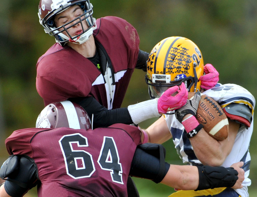 Nokomis High School defenders Mike Massow (1) and Jake SeeHusen (64) tackle Mt. Blue High School's Christian Whitney (28) on Saturday in Newport.