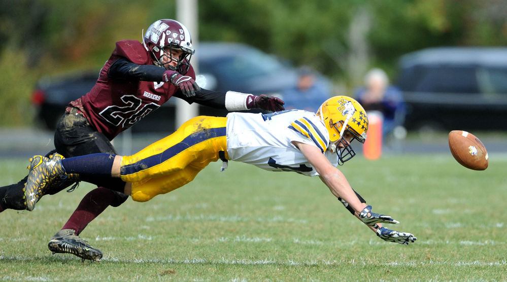 Mt. Blue High School's Nate Pratt-Whitney (14) dives for the ball as Nokomis High School's Colby Pinette (20) defends on Saturday in Newport.