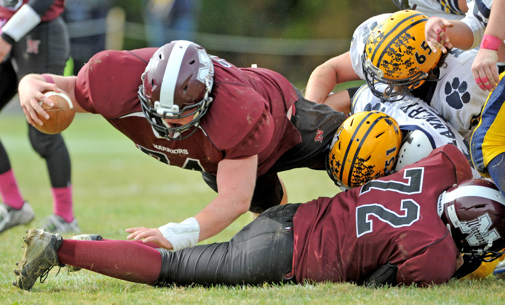 Nokomis High School's Alex Chapman (74) dives for extra yards as Mt. Blue High School's Leo Flannery (51) and Adam Mealey (65) defend Saturday in Newport.