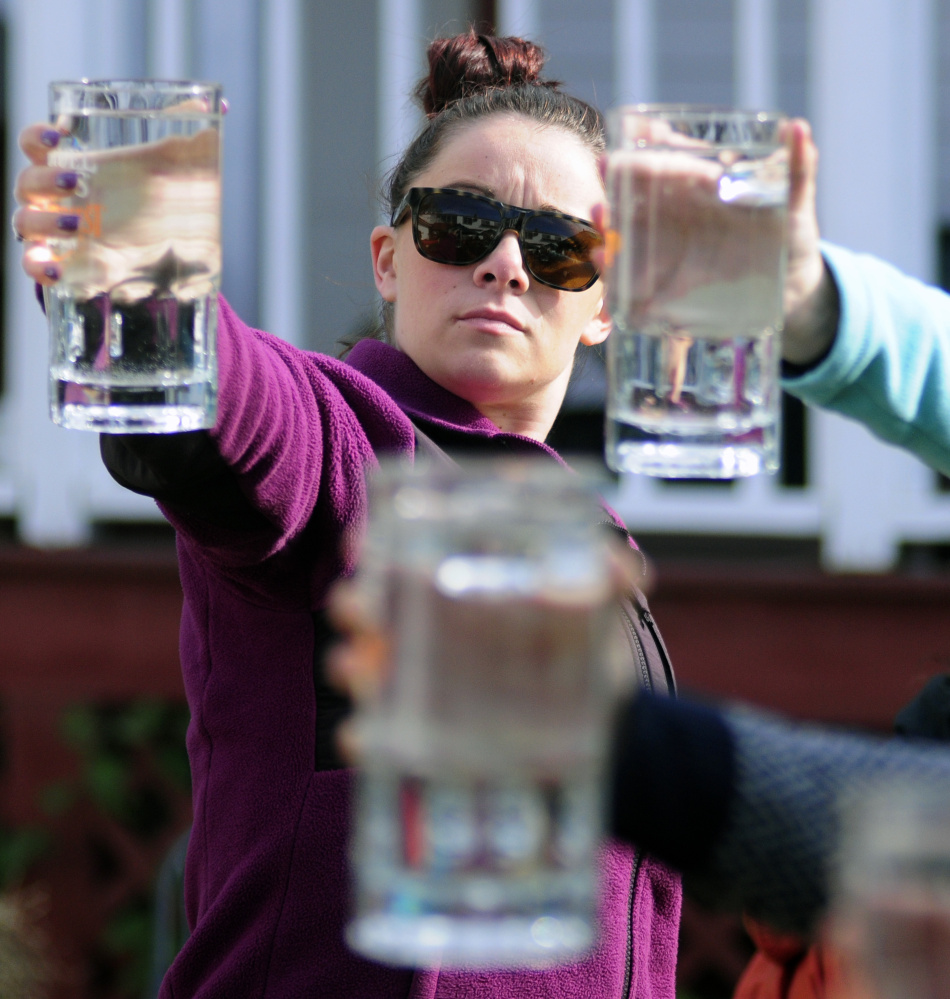 Kaitlin Sweeney holds up a 44-ounce mug as she competes in the stein hoisting contest during harvest festivities on Saturday in Belgrade Lakes village.