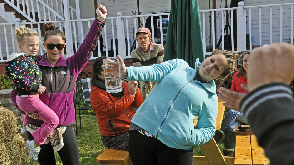 Laila Ring, left, and Kaitlin Sweeney cheer on Laila's mother, Devhan Ring, as she wins the stein hoisting contest during harvest festivities on Saturday in Belgrade Lakes village.