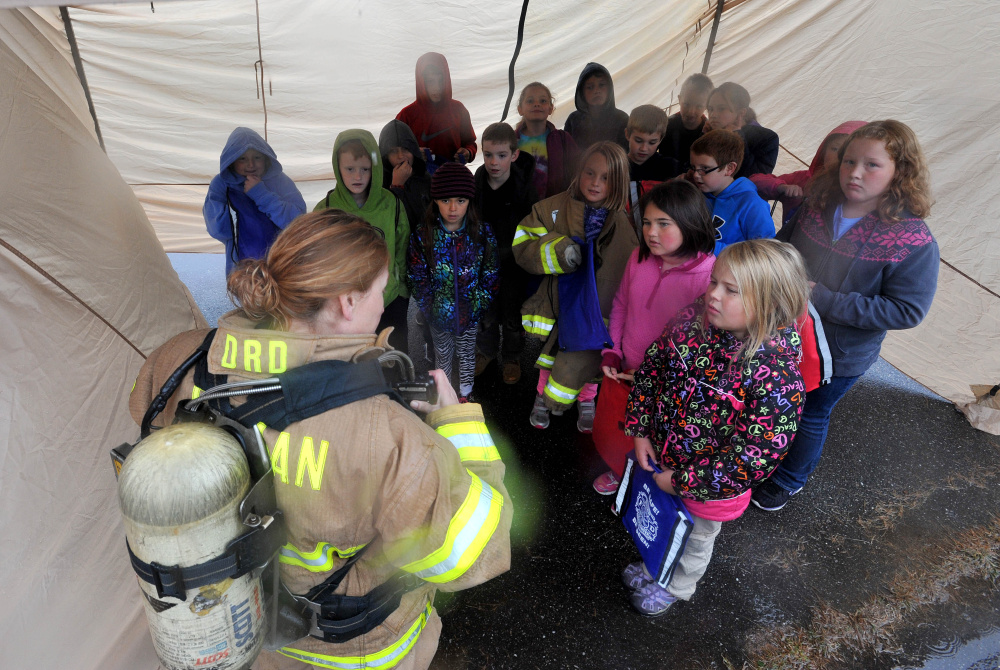 Firefighter Nancy Otis shows fourth-graders how her personal safety equipment works during a fire safety course at Canaan Elementary School in Canaan on Friday.