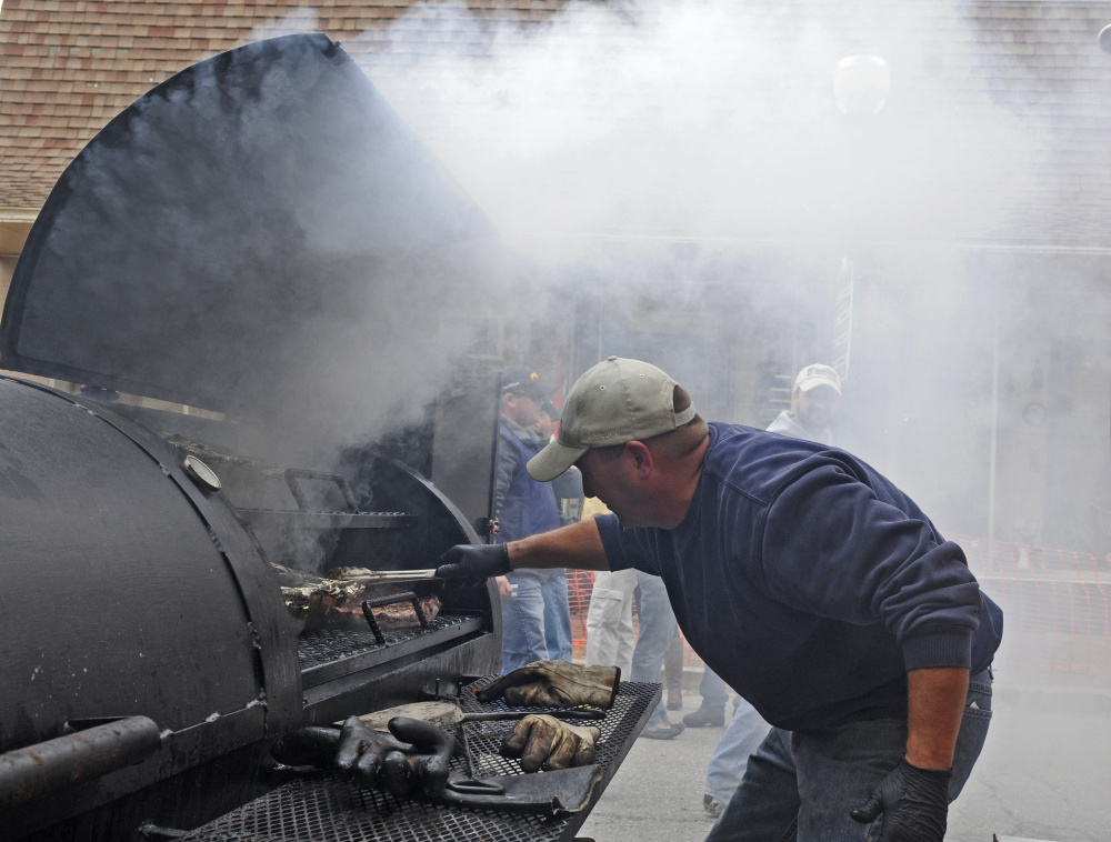 Kris Levasseur tends meat in the smoker at the K and D Barbecue booth during the Swine and Stein festivities on Saturday on Water Street in downtown Gardiner.