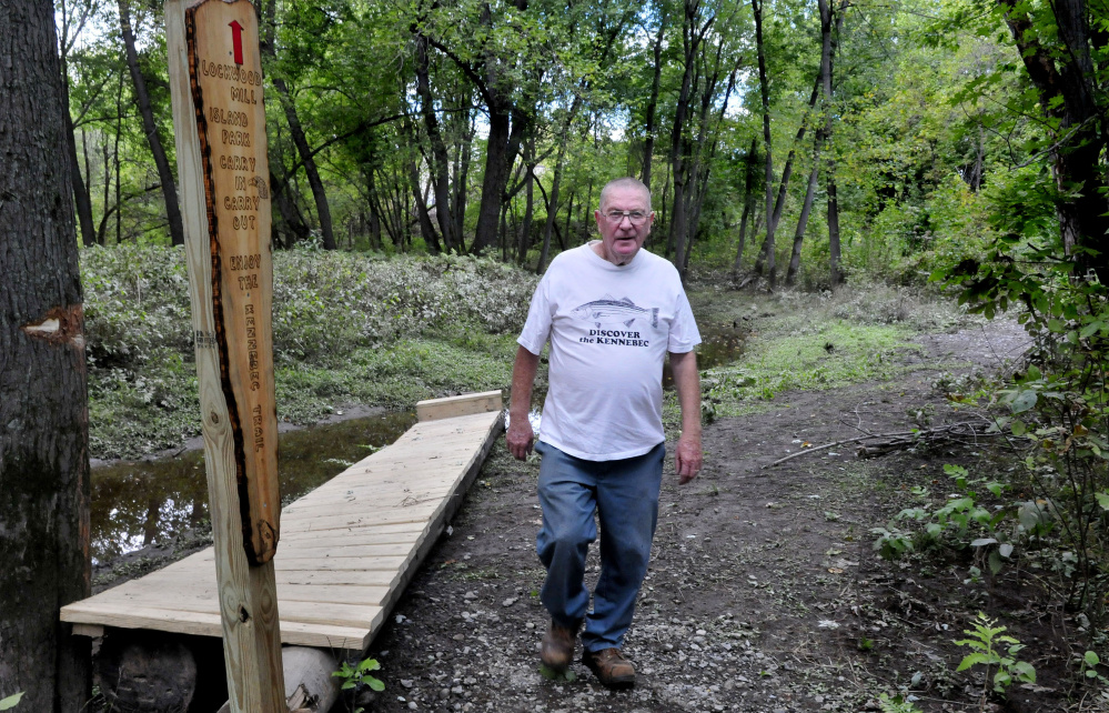 Charlie Poulin walks along the Kennebec Trail in the Lockwood Mill Island Park in Waterville recently near one of the wooden signs he made.