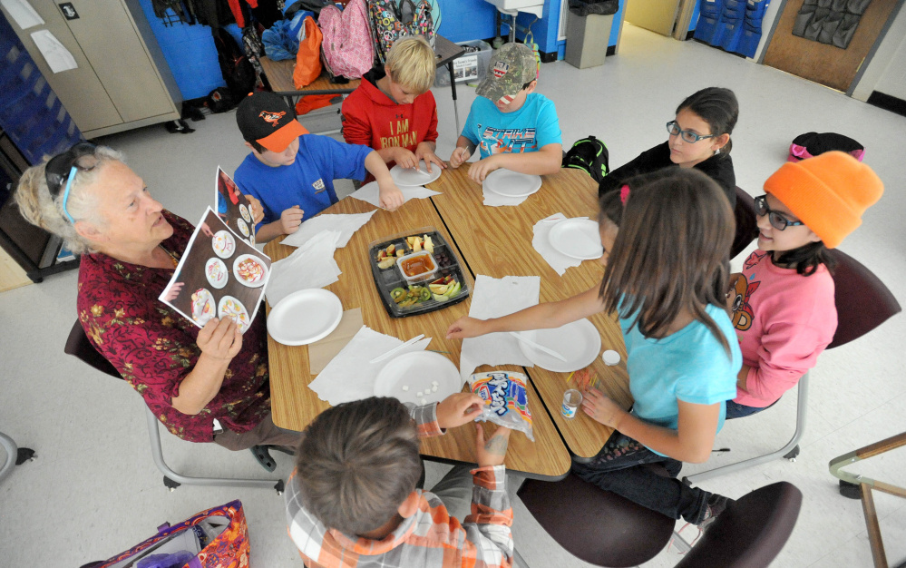 Sally Baker, left, shows examples of edible art to a group of fifth-graders during art class at Cornville Charter School in Cornville on Wednesday. Every Wednesday for two hours students at the Cornville school get hands on instruction from two artists and two musicians who visit students in groups.