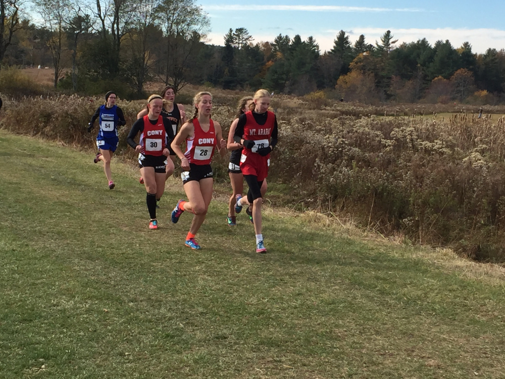 Staff photo by Randy Whitehouse   Cony's Anne Guadalupi, left, runs with teammate Talia Jorgensen, behind, during the Class A North cross country championships in Belfast on Saturday. At right is Mt. Ararat runner Katherine Leckbee.