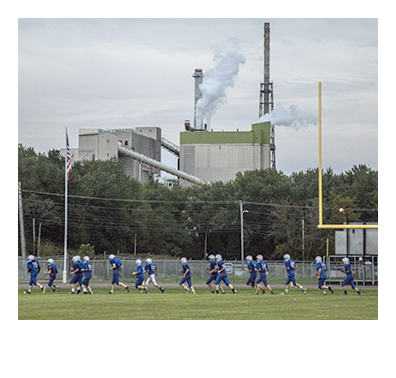 RUMFORD, ME - OCTOBER 1: The Mountain Valley High School football team runs around the perimeter of Hosmer Field before practice, with the paper mill in the background in Rumford, ME on Thursday, October 1, 2015. (Photo by Whitney Hayward/Staff Photographer)