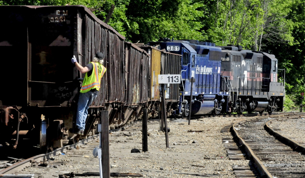 A Pan Am Railways car pulls away at the Waterville yard  in July. A Winslow man who worked in the yard has sued the company, saying he was fired the day he asked for leave because of cancer treatment.