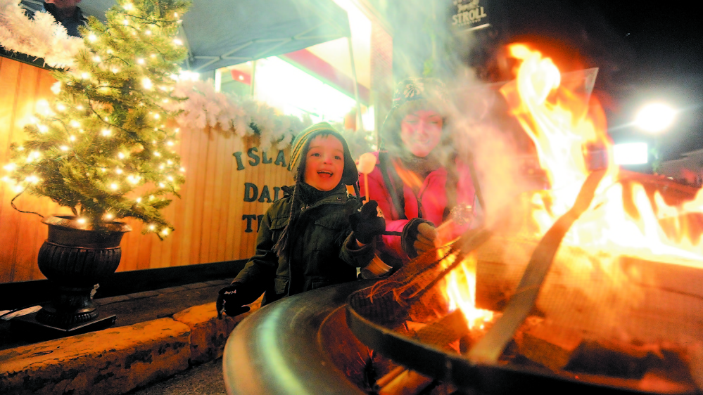 Christina Easler, right, and her son Gavyn, 4, enjoy a hot marshmellow over an open fire on Water Street at the 2013 Holiday Stroll in Skowhegan. This year's kicks off Friday.