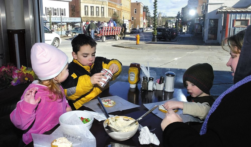 Part of the annual Holiday Stroll in Skowhegan last year was cookie decorating at the Empire Grill. From left to right is Isabella Mullen, 2, her brothers Isaiah Cole, 6, Noah Cole, 2, and their mother Heidy Mullen. This year's two-day event begins Friday.
