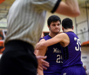 Waterville's Devon Begin, right, celebrates with teammate Justin Kornsey after Kornsey drew a sank a shot and drew a foul during a game Friday night at Winslow.
